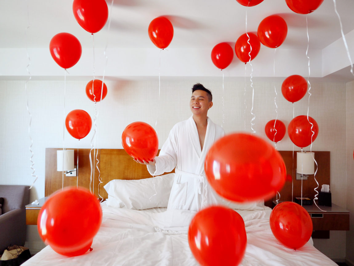 Michael in a hotel room with red balloons