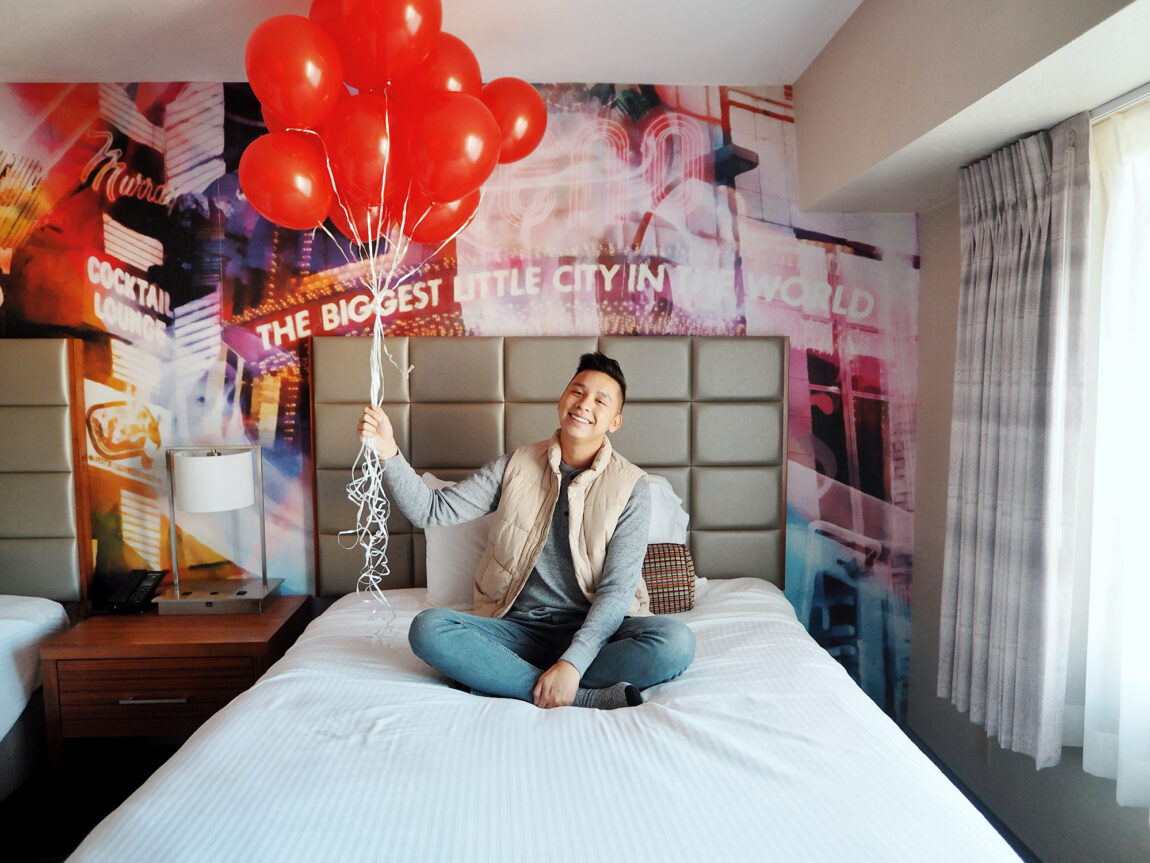 Michael sitting in Circus Circus room with red balloons.