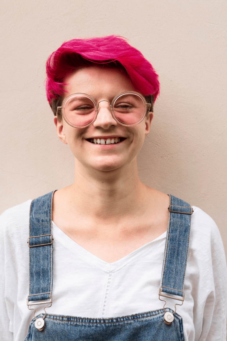 smiling human with pink hair and glasses wearing overalls