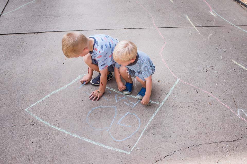 Boys make chalk drawings in an East Grand Rapids driveway during a family documentary session