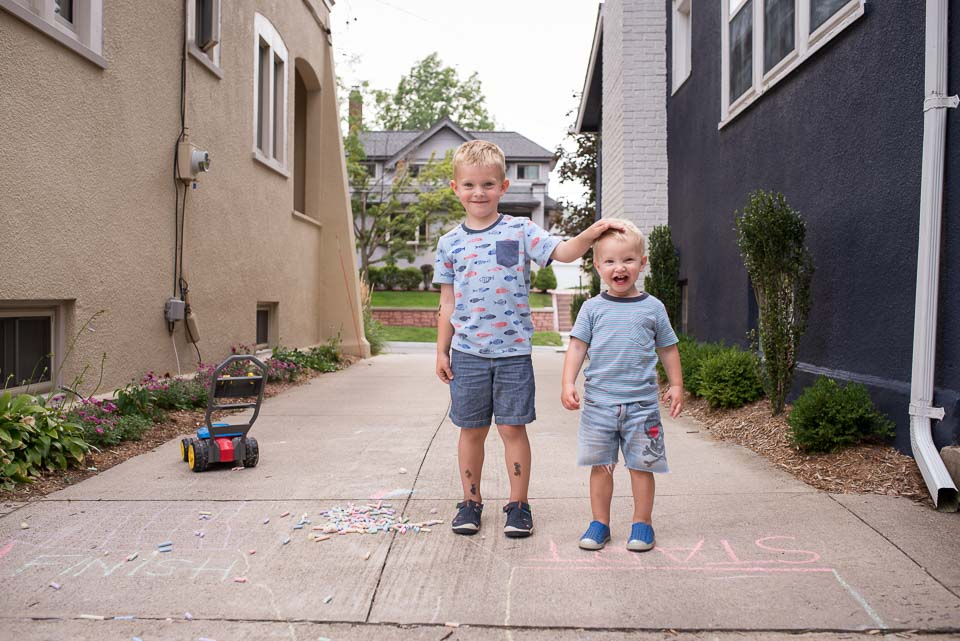 During a family documentary photo session two boys stand beside driveway chalk drawings and laugh