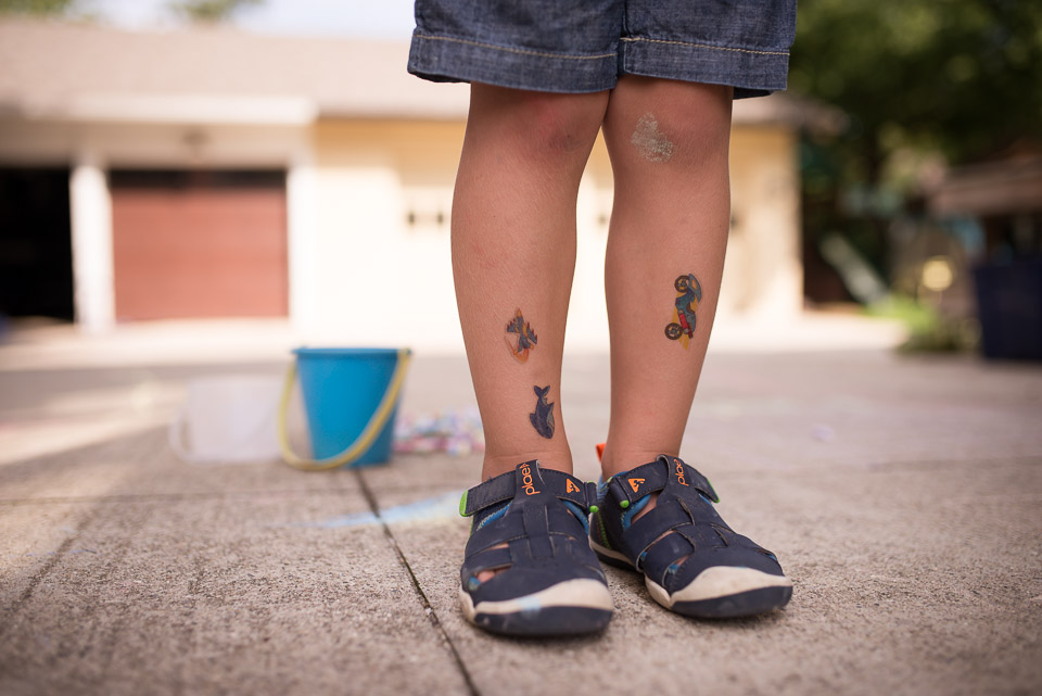 Close up documentary family photo of fake tattoos on a young boys legs