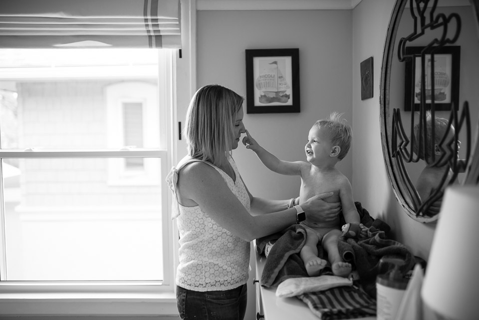Boy pinches mothers nose while she dresses him in this family documentary photography picture