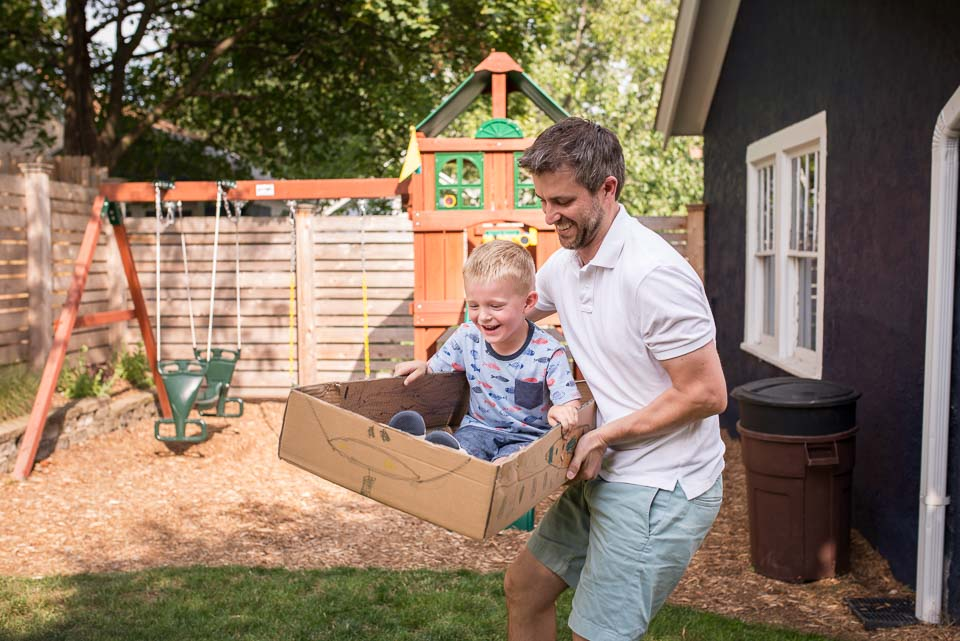 Father flies son in a cardboard spaceship during Grand Rapids family day in the life session
