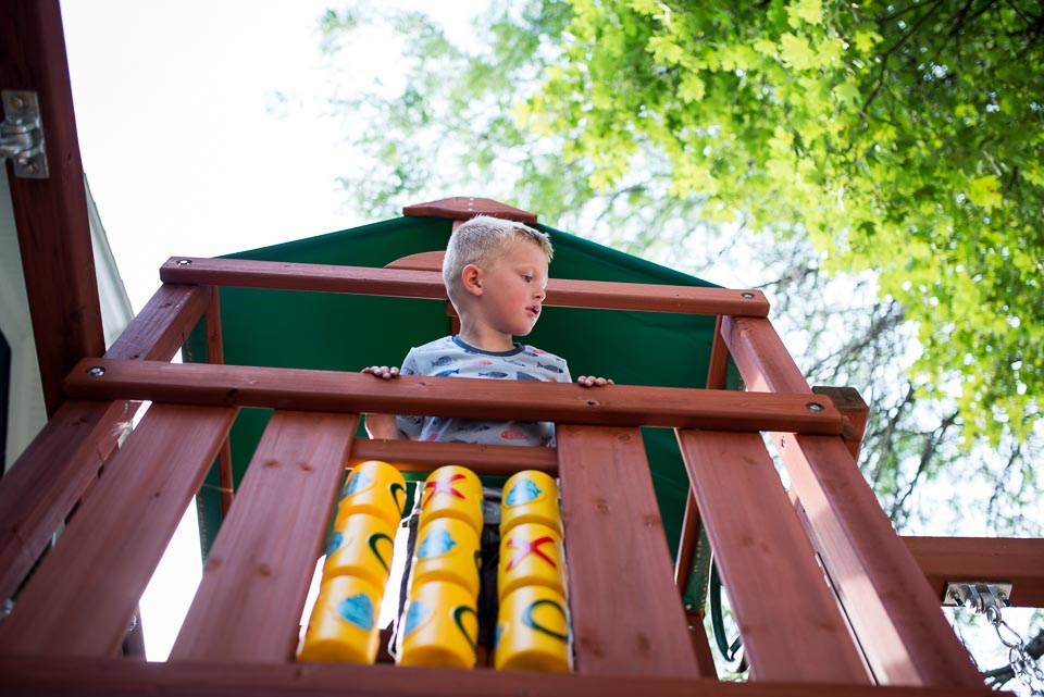 Boy plays in fort during day East Grand Rapids in the life family documentary picture session