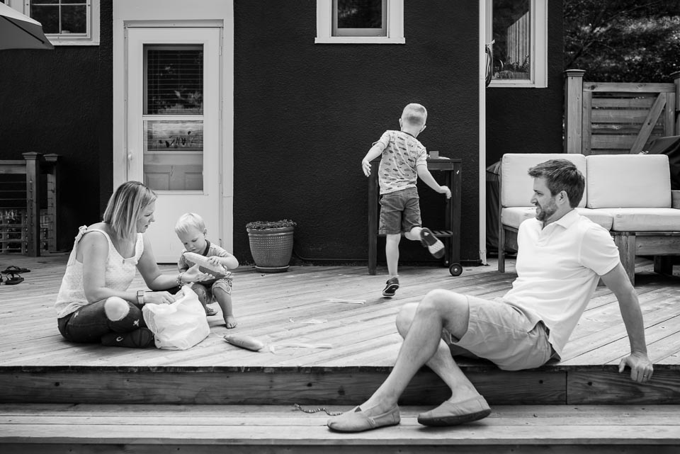 Family of four relax on their deck while a Grand Rapids documentary photographer photographs them