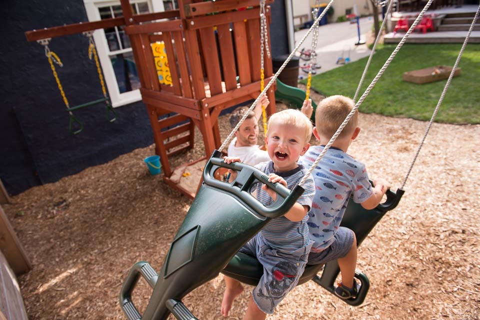 Two boys swing and laugh during a Grand Rapids day in the life family documentary session