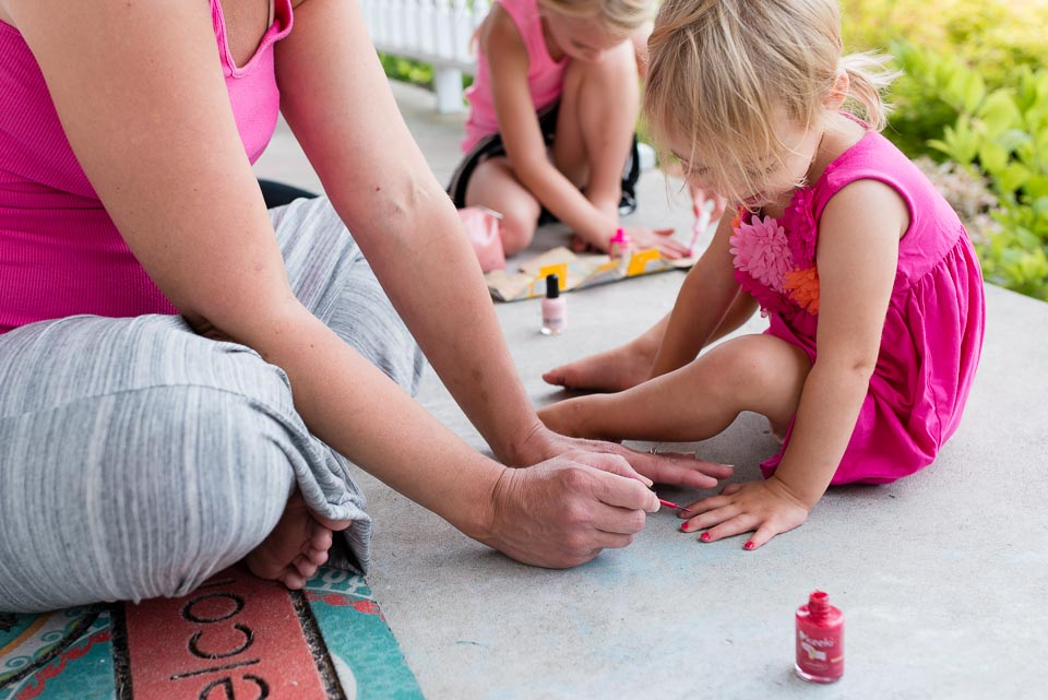 Mother paints a child's toenails during a day in the life session near Grand Rapids