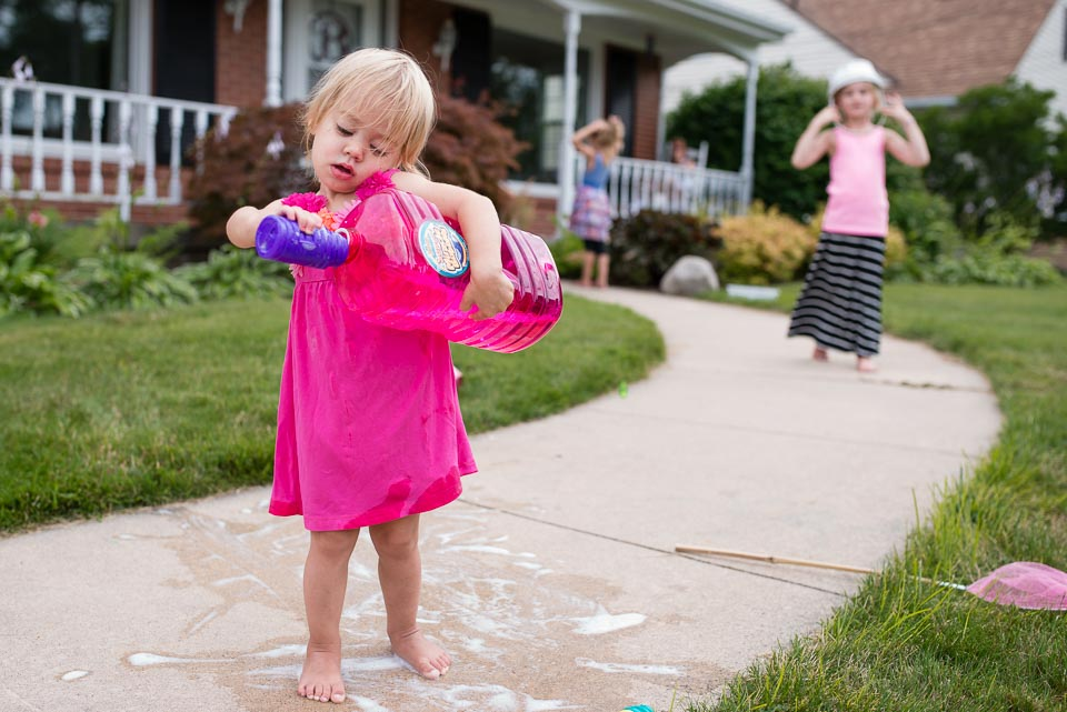 Grand Rapids family documentary image of young child spilling bubble solution while filling a smaller container