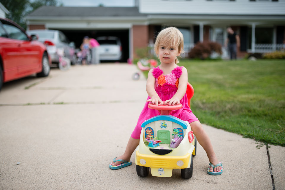 Girl astride a toy car in front of their Grand Rapids home for documentary family session