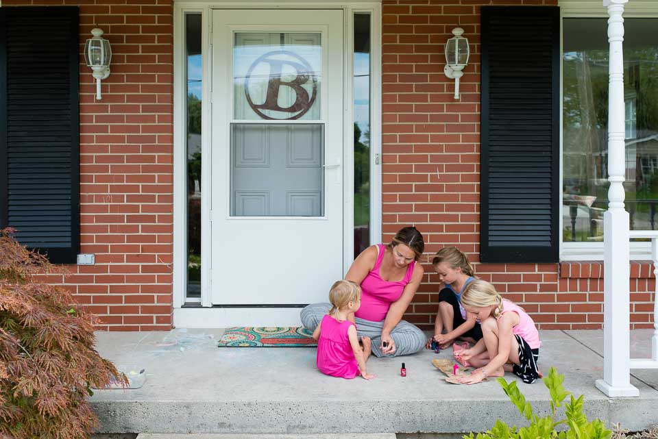 Mother and girls paint their nails on a Grand Rapids porch during family documentary session