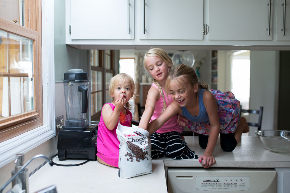 Girls sneak chocolate chips in this image by a Grand Rapids family documentary photographer