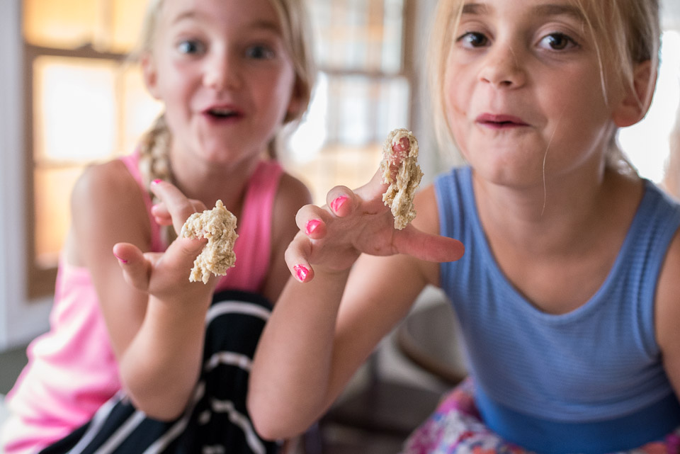 Two girls display cookie dough covered fingers to family documentary photographer during a family session