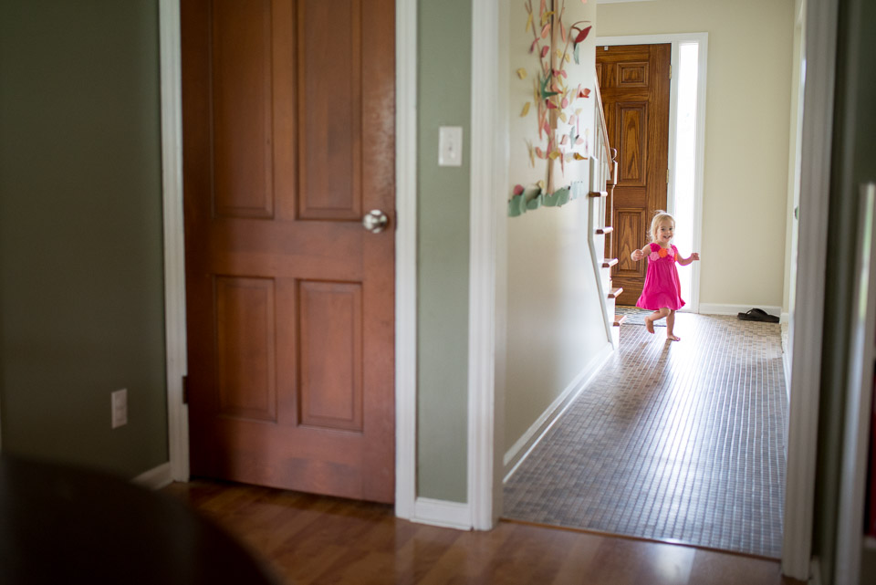 Young child runs through the house during a family documentary photography session near Grand Rapids
