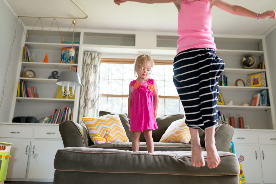 Sisters jump from the couch in a West Michigan family documentary photography session