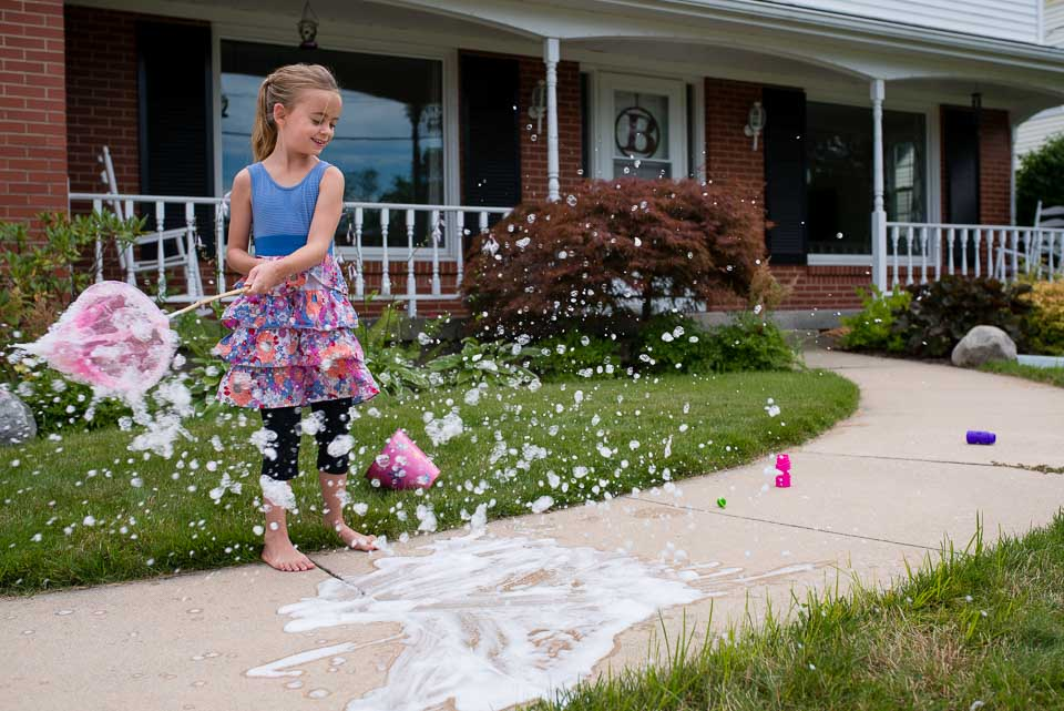Girl waves a net to create bubble foam during a family documentary session