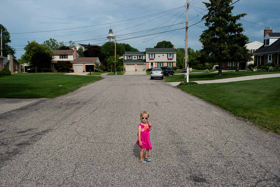 Small child wears sunglasses and stands in the road during a family photojournalism session