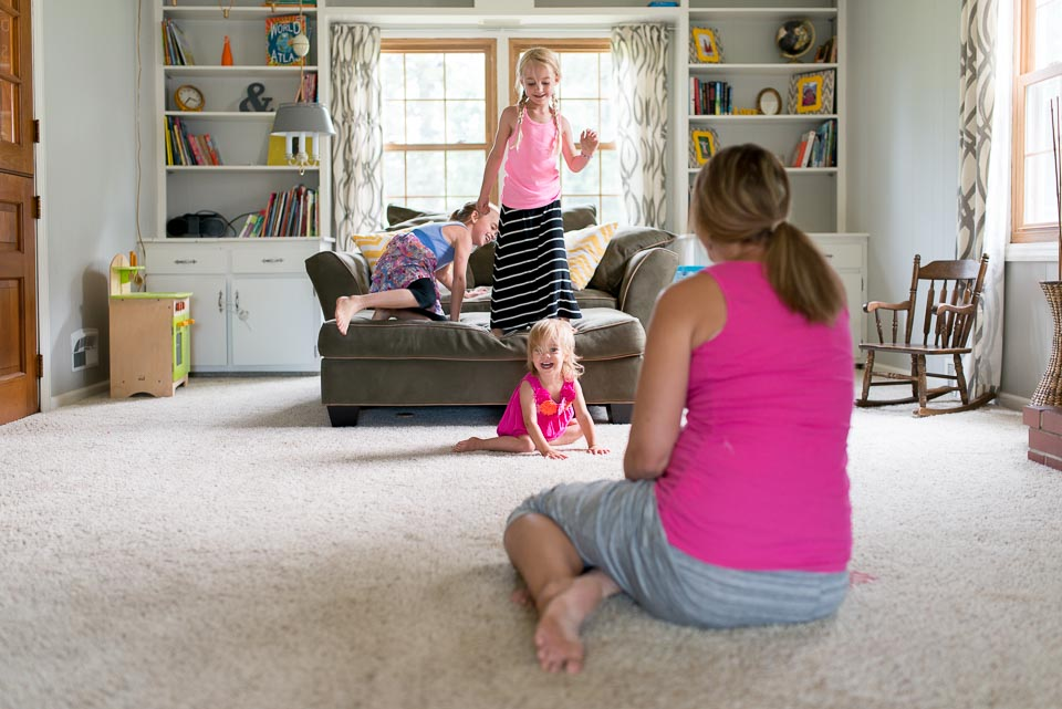 Grand Rapids mother watches children play in a family day in the life photography session