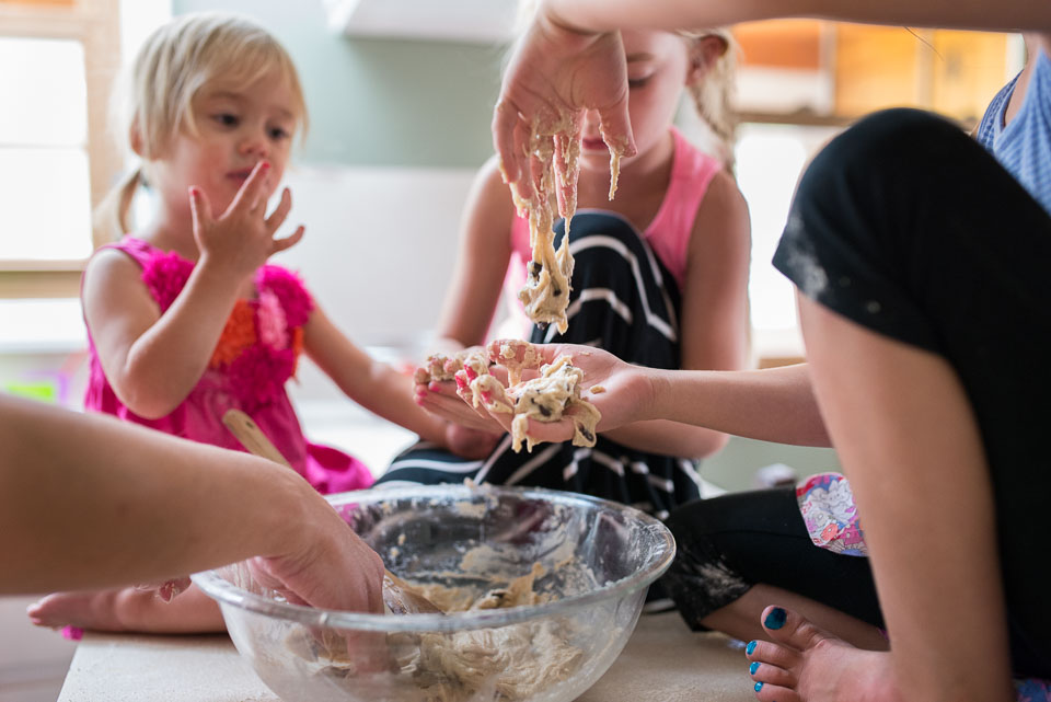Cookie dough dangles from a child's fingers in the Grand Rapids family documentary photograph
