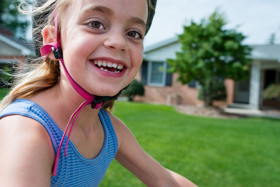Girl grins as she rides her bike past the family documentary photographer