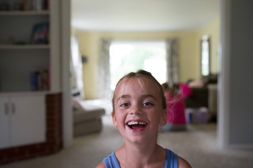 Young girl smiles at the family documentary photograper.