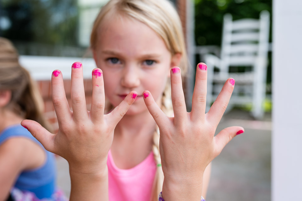 Child displays her painted nails during a family documentary day in the life photography session