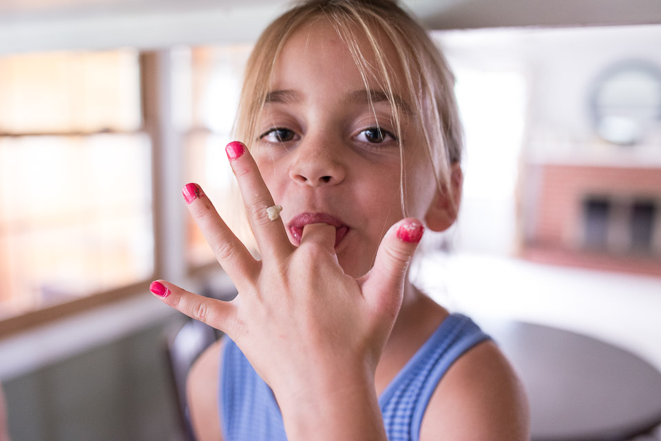 Grand Rapids child licks cookie dough from fingers during day in the life documentary session