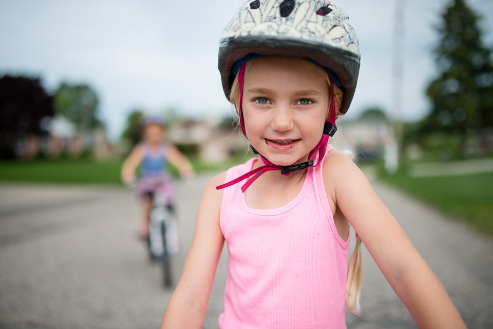 Girl wearing a bike helmet gazes into camera during Grand Rapids day in the life session