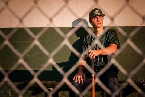 Baseball player poses for senior portraits by Grand Rapids senior portrait photographer