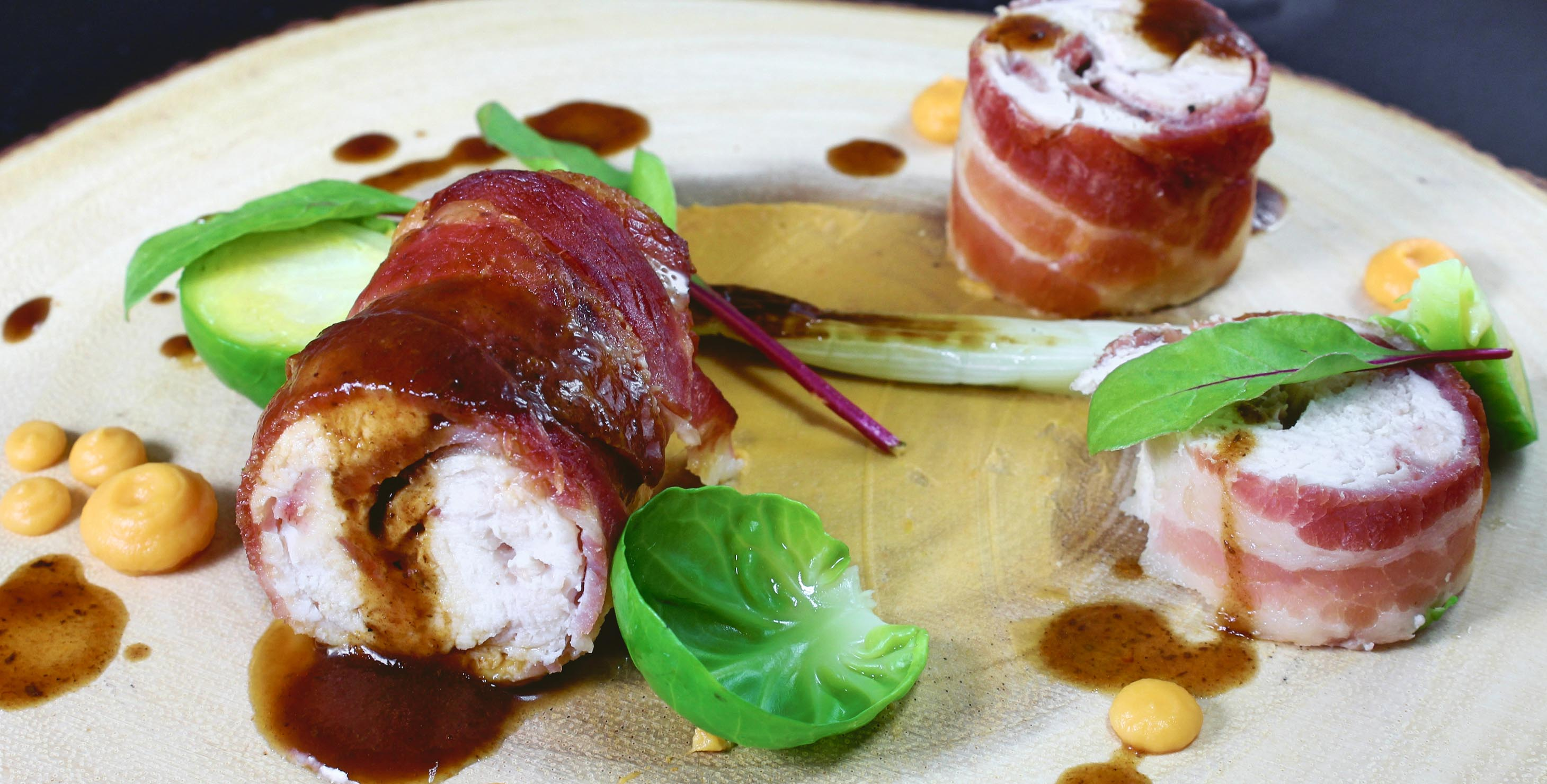Bacon wrapped stuffed chicken on a wooden cutting board