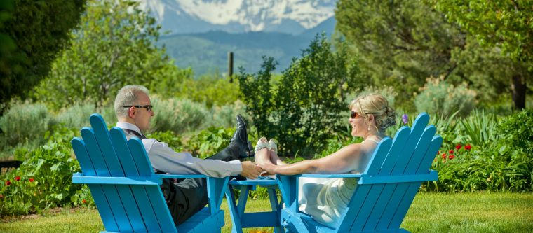 Elopement couple sitting on blue wooden chairs in a garden with mountains in the distance