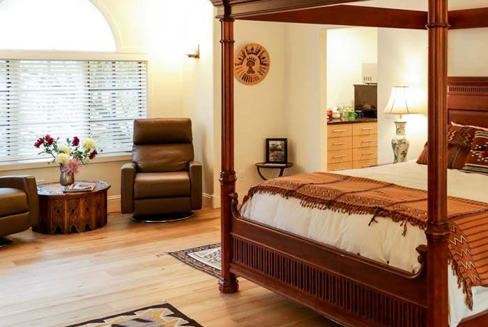 4 poster king size bed in a spacious room with hardwood floors