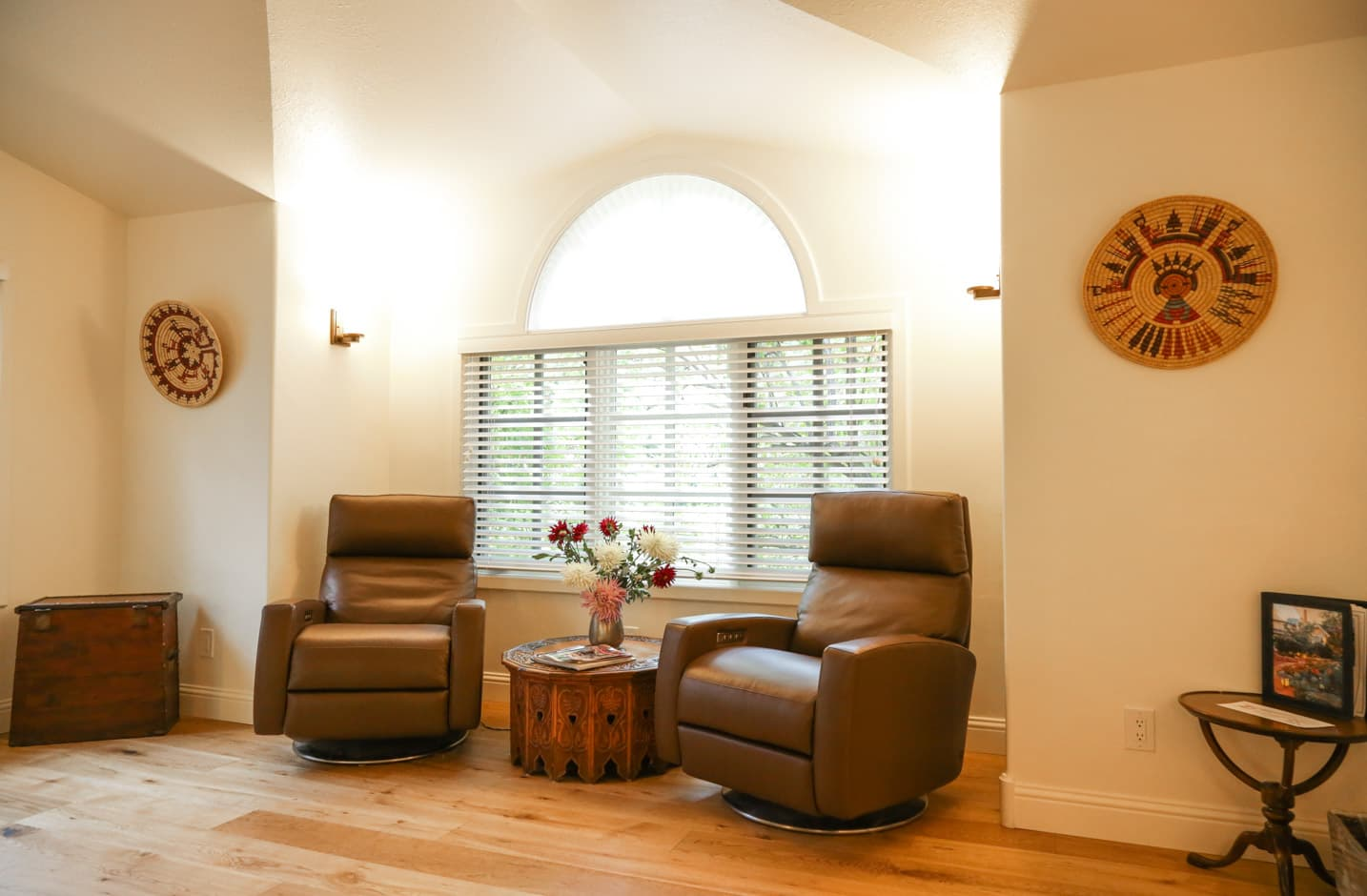 Two leather chairs with a end table and high ceilings