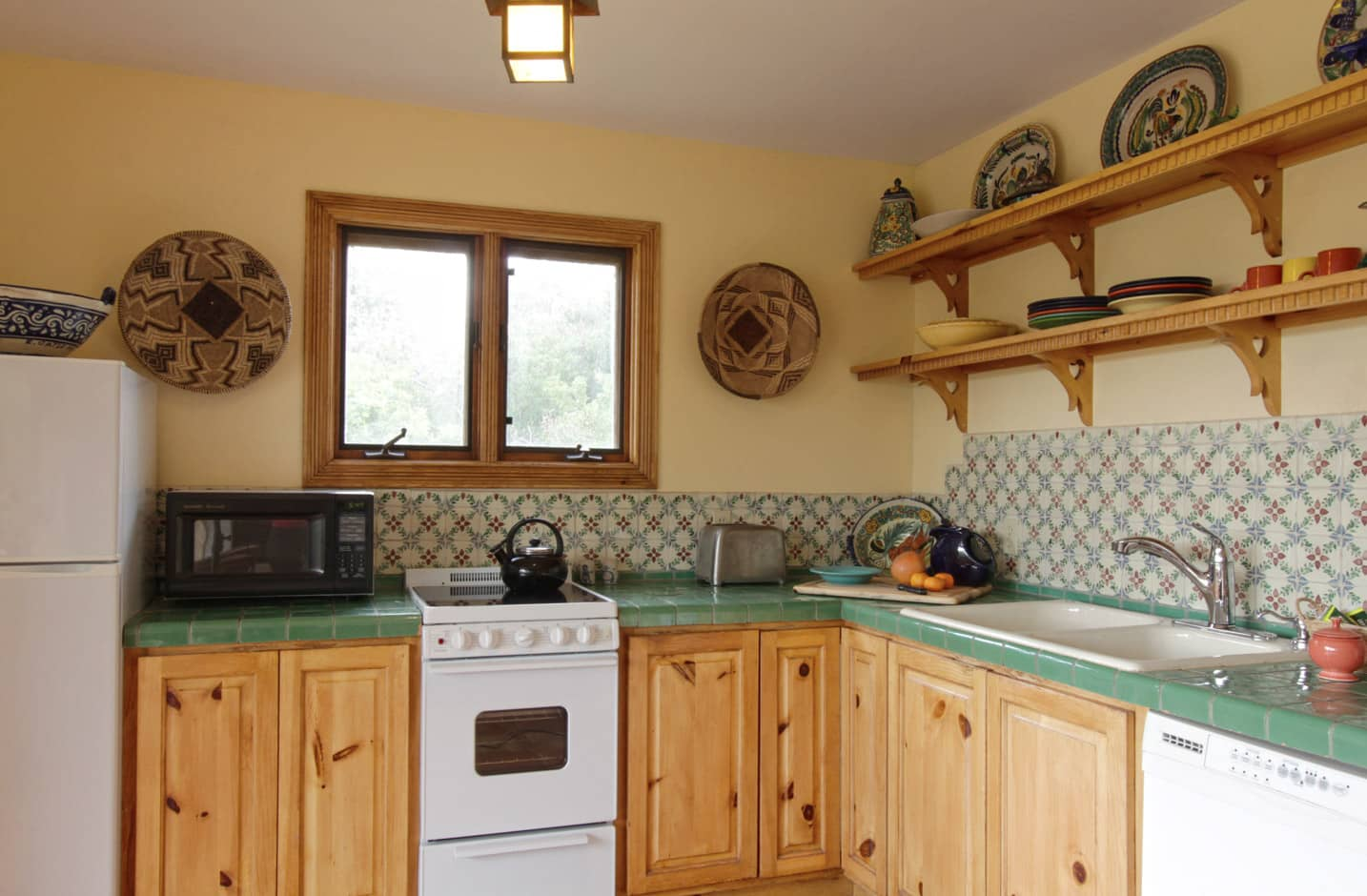 An L shaped kitchen with dishwasher, range, and window