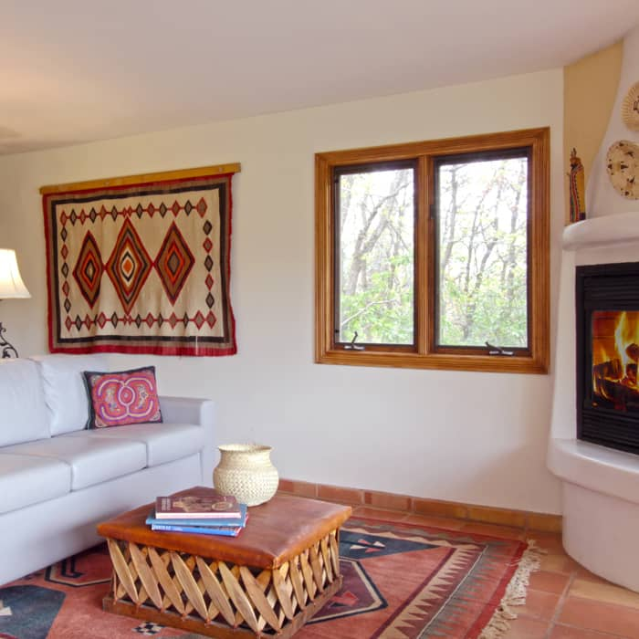 A large living room with a geometric rug a large couch and fireplace