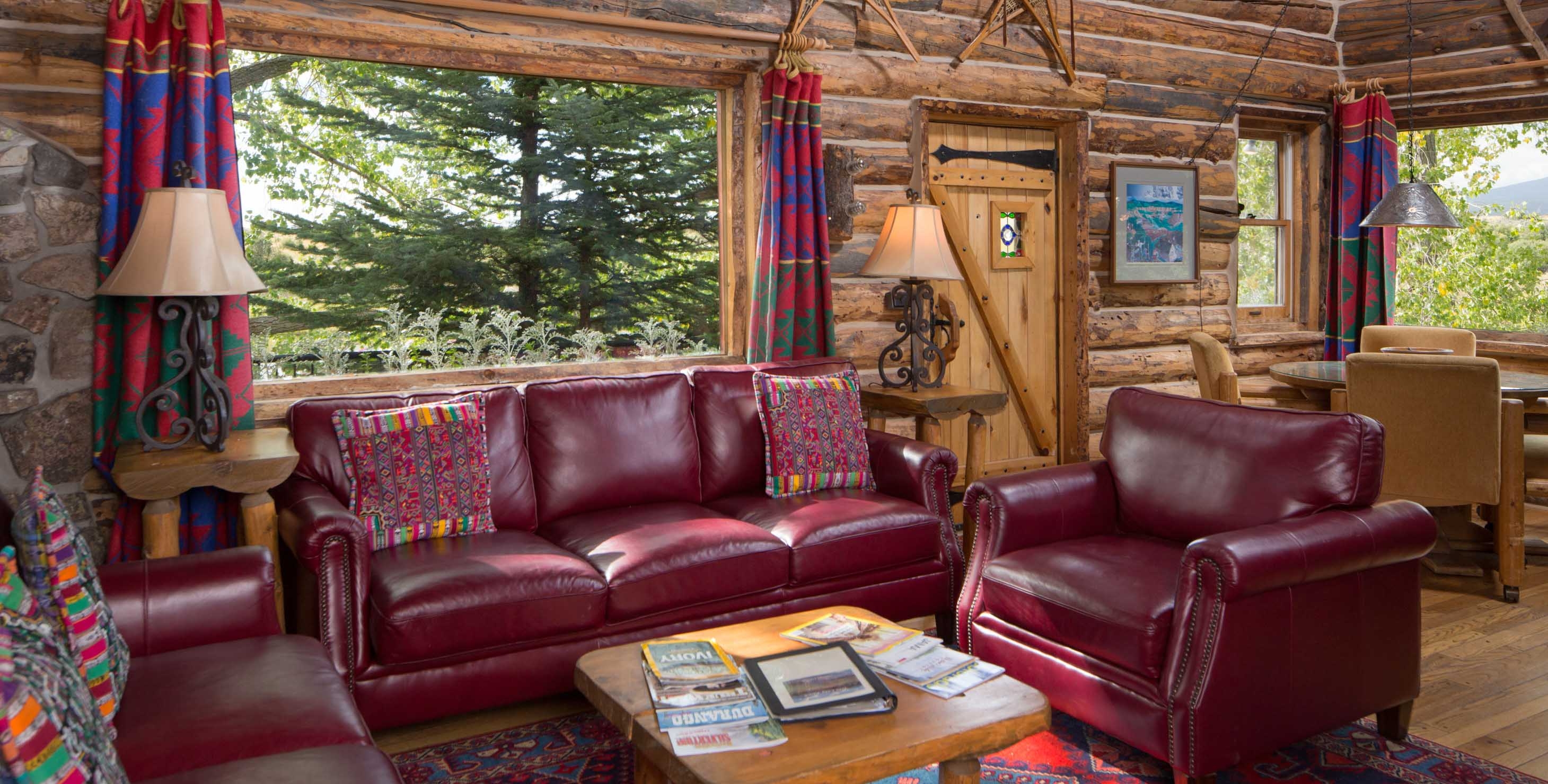 Living room in a log cabin with red leather couches and large windows