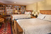 A large room with two queen beds and a bookshelf