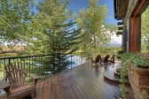 Second Story deck with wooden chairs overlooking a lake