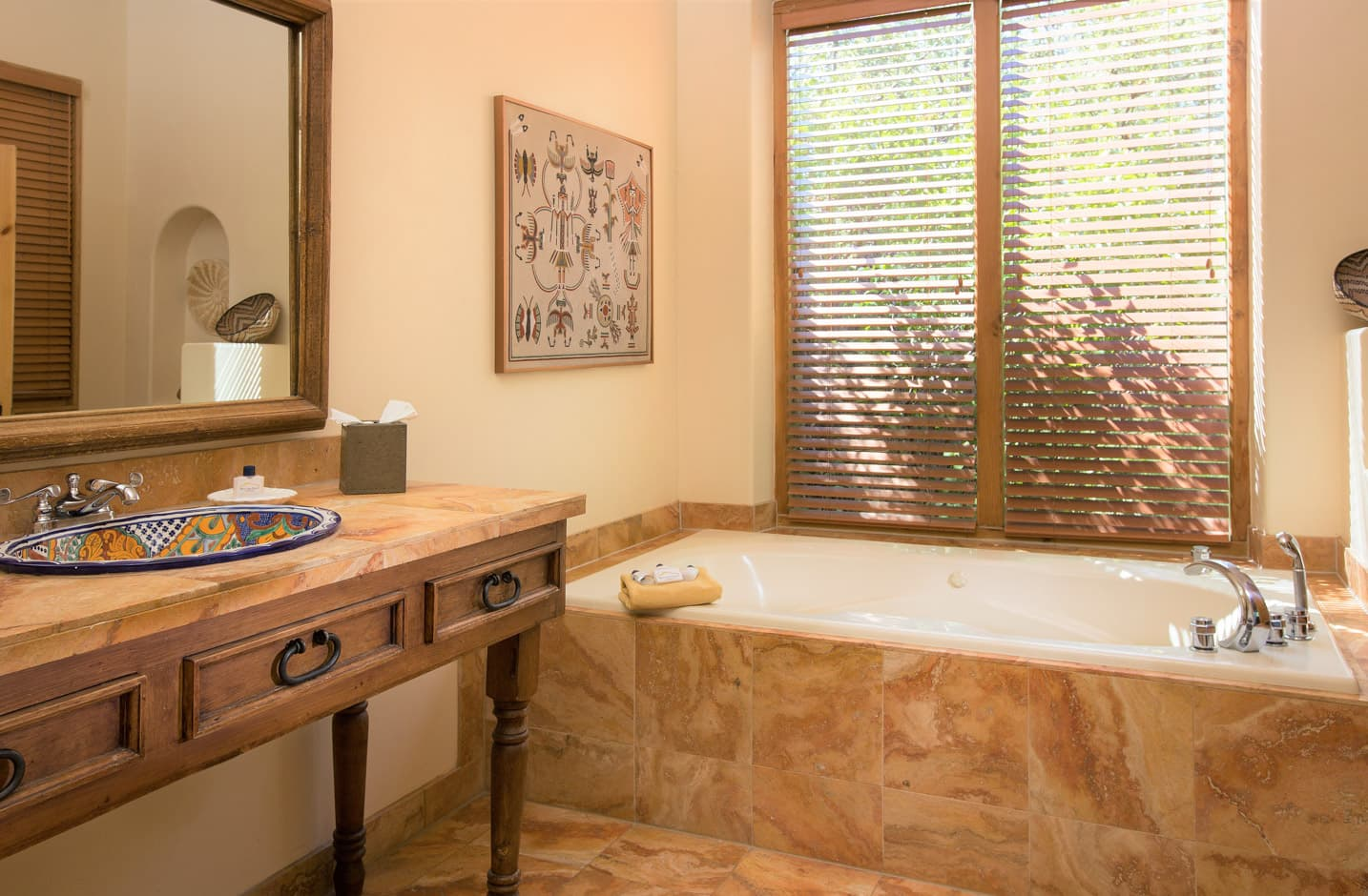 A bathroom with a large tub and a sink and mirror