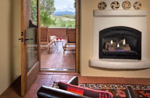 A gas firplace and a patio with two chairs and mountain views
