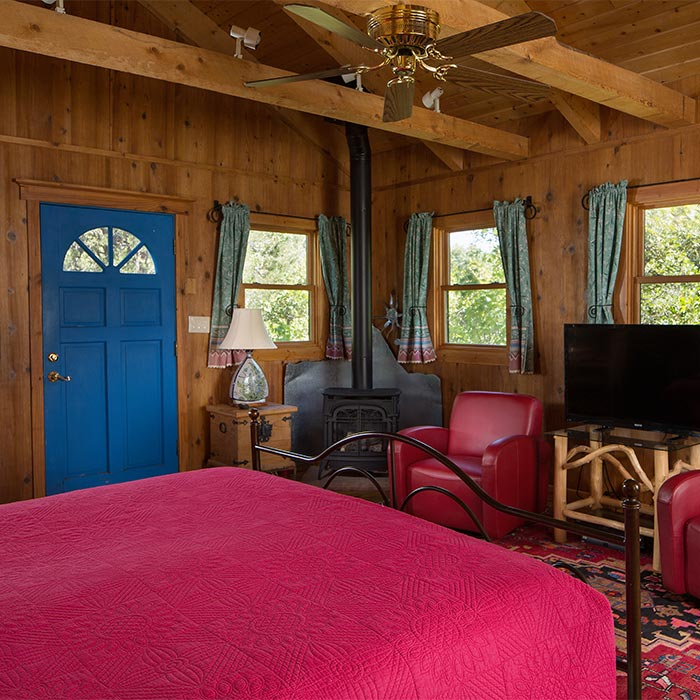 A cabin with a king bed ceiling fam, and flat screen TV