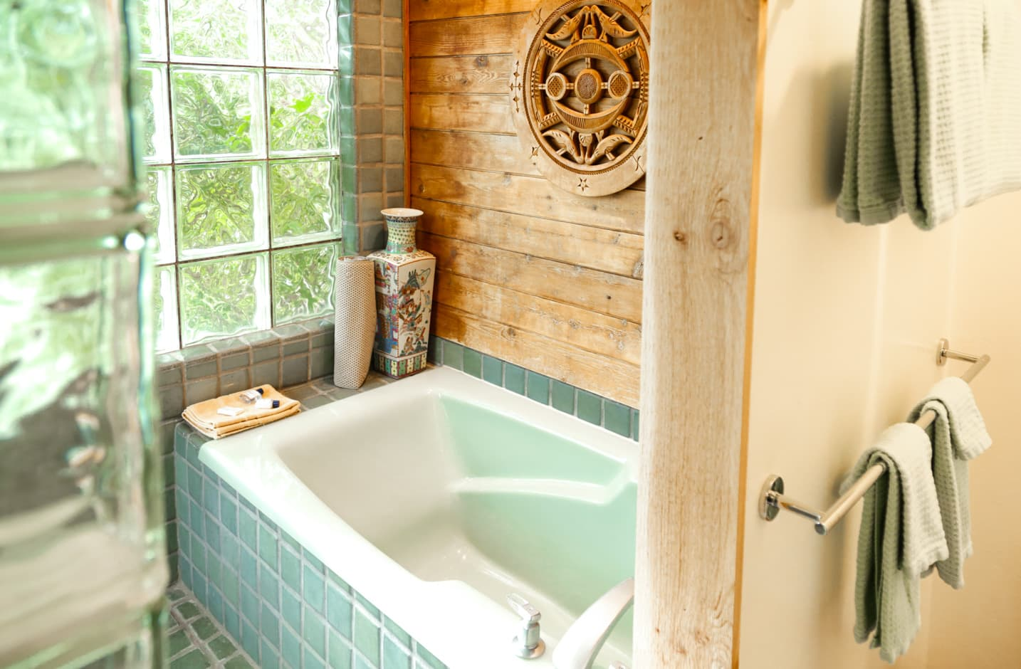 Large tub in a garden room with wooden walls and tile floors