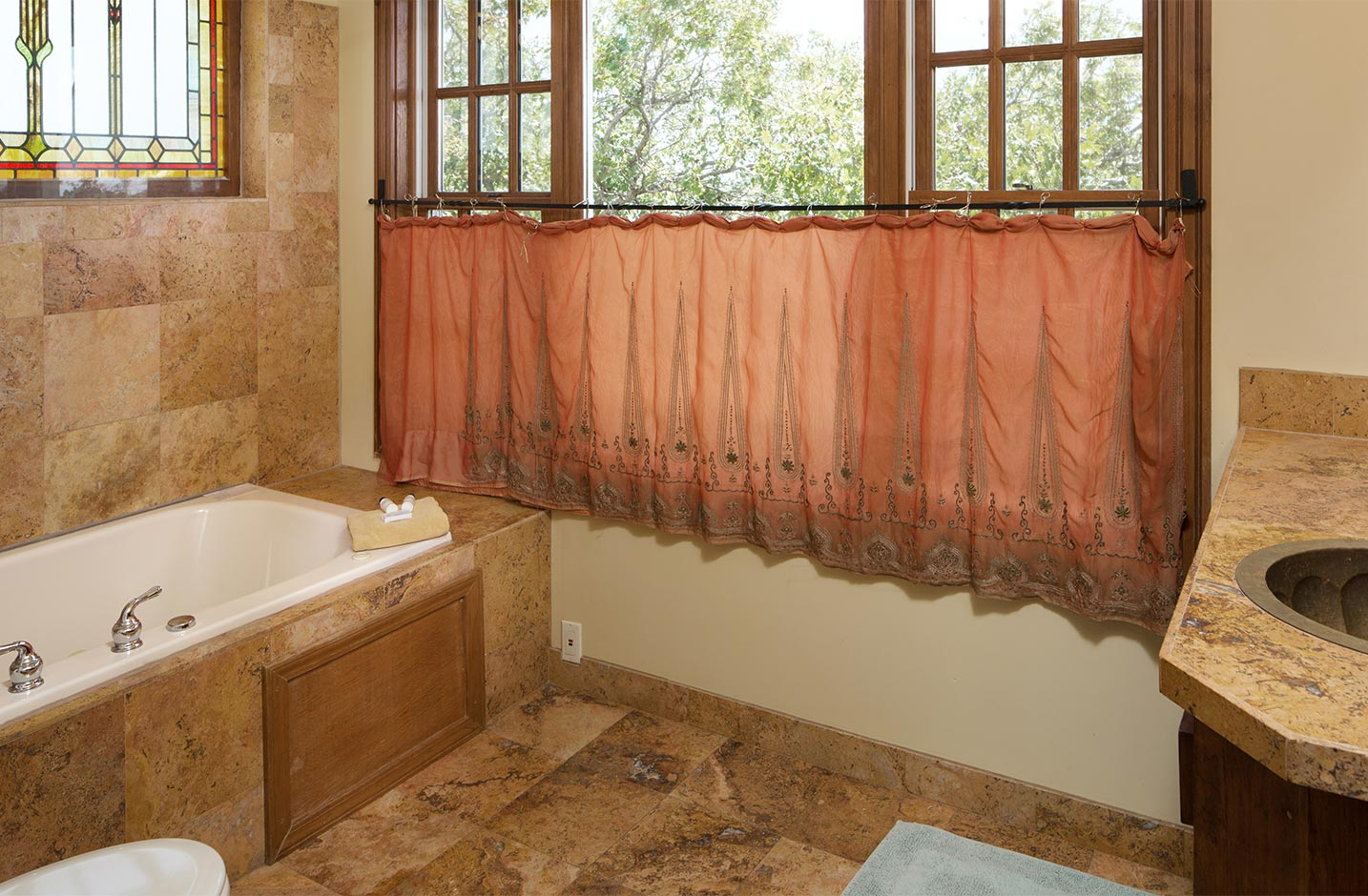 Bathroom with a large tub and windows