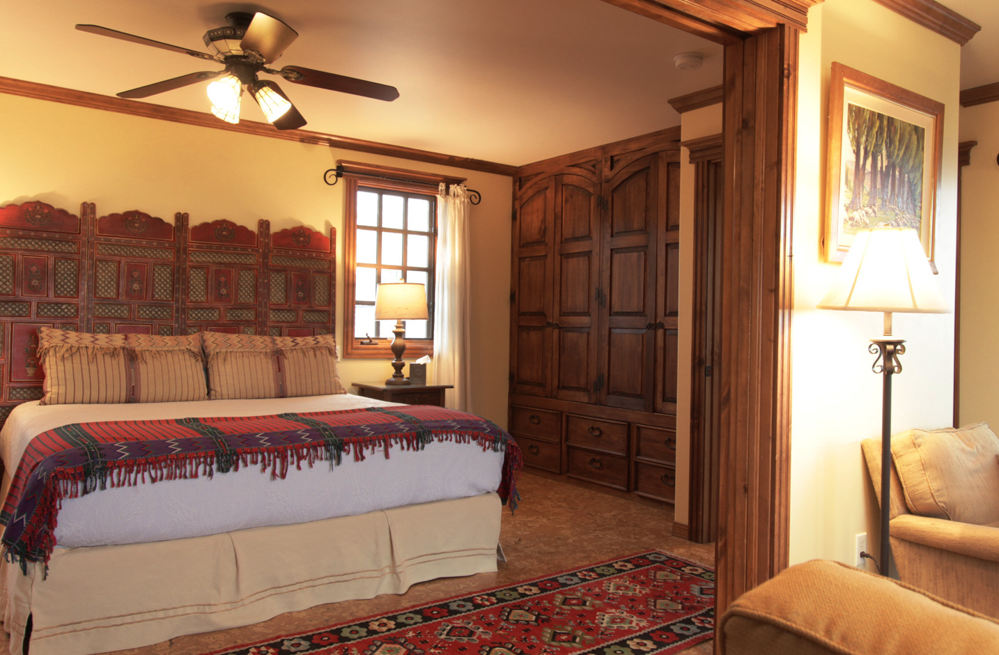 A large room with a king bed and ornate headboard