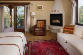 Spacious room with a king bed, fireplace, seating area, and balcony