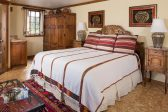 A spacious room with a king bed and side table
