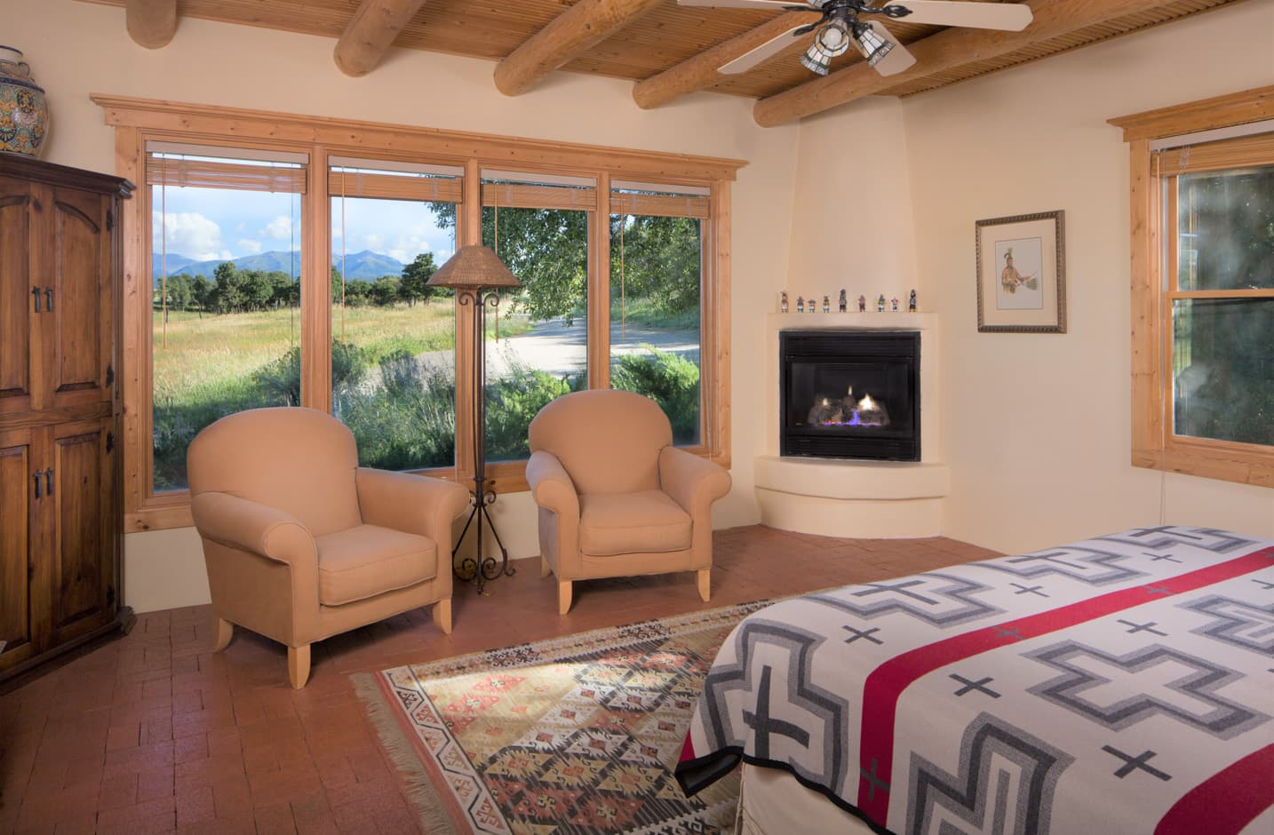 Bedroom with a gas fireplace in the corner and two chairs