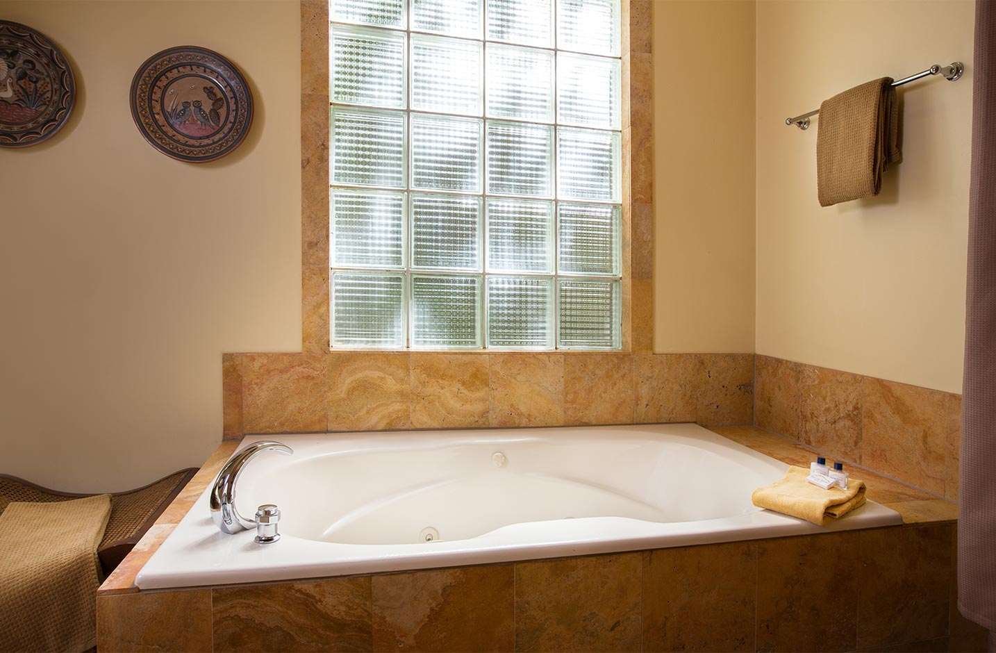A Whirlpool tub with a glass block wall in a spacious bathroom