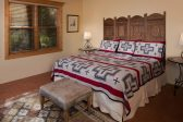 A king size bed with wooden headboard and two side tables with lamps and a bench at the foot of the bed
