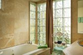 A bathroom with glass tile and a large bath tub